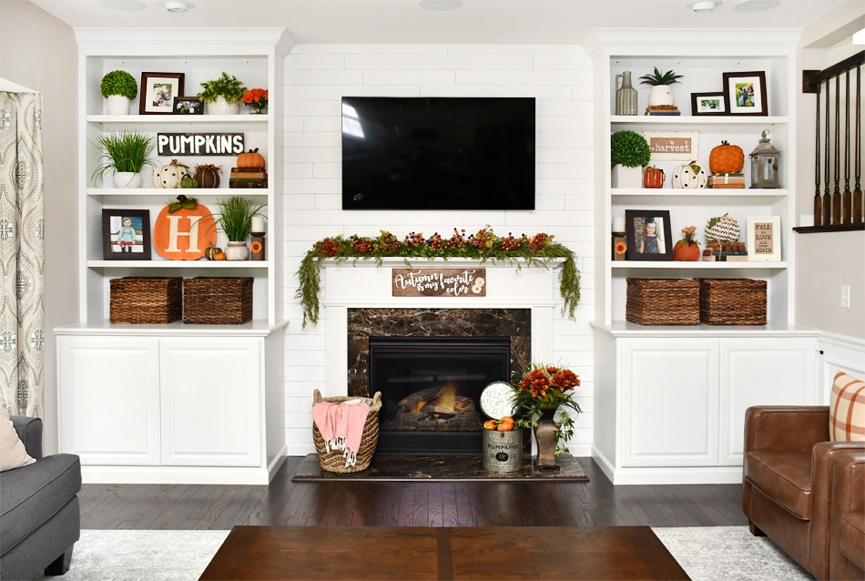 The all white bookshelves and fireplace with a tv above it.