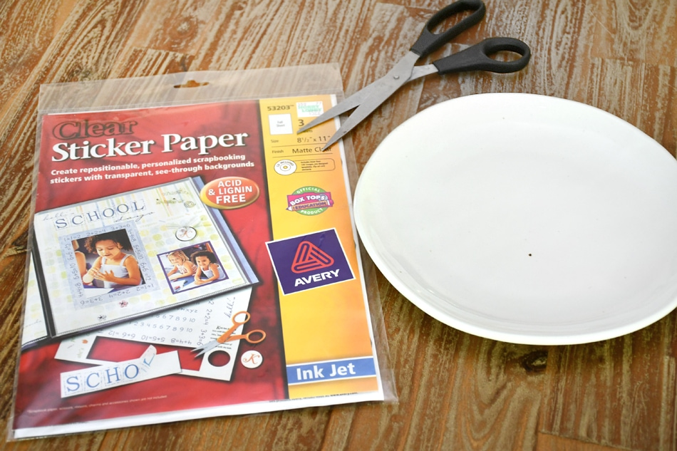 A white plate, stickers and scissors on a table.