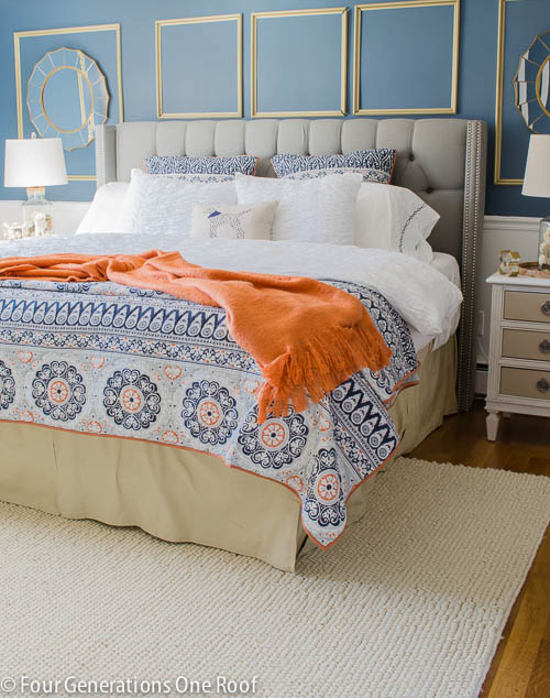 Blue walls and blue and orange blankets in bedroom.