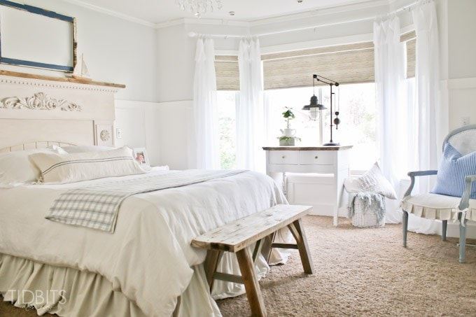 All white bedroom with light blue pillows on chair.