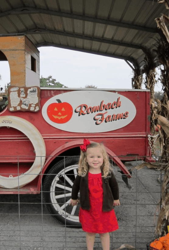 Blonde girl with a red bow in front of a red truck at the pumpkin patch.