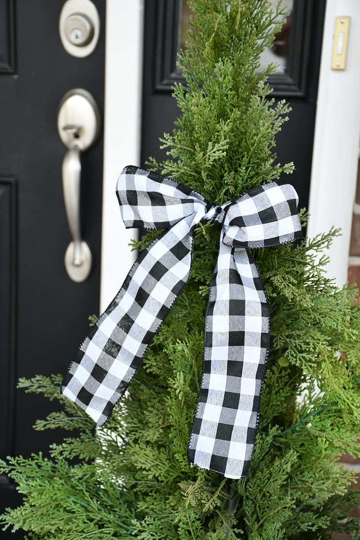 Large tree planters with a checkered bow tied around it by the front door.