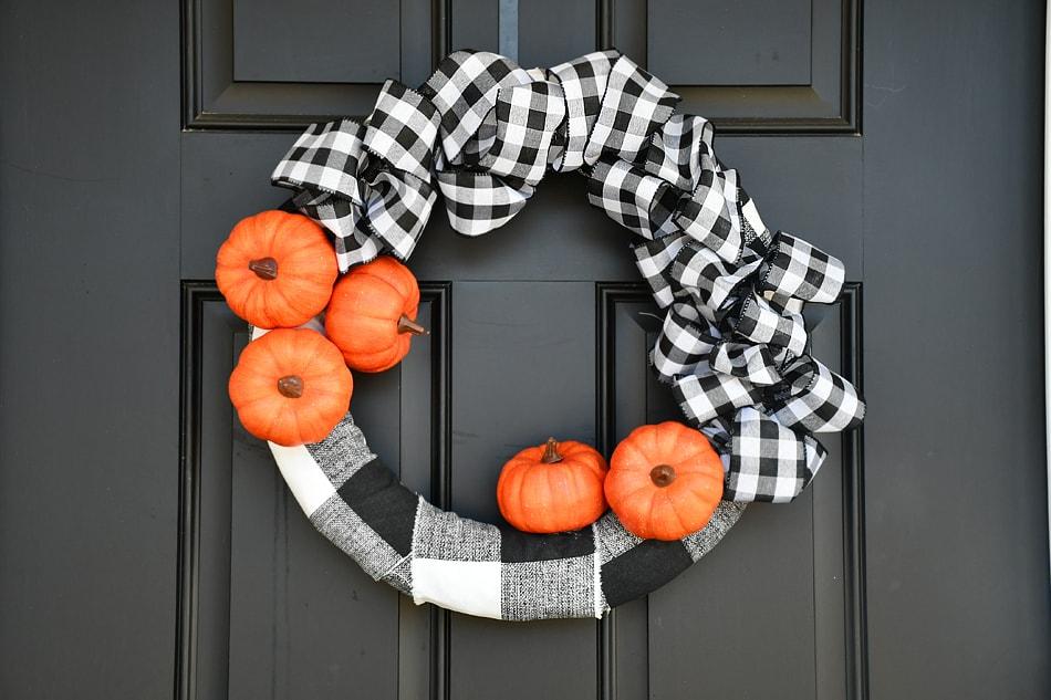 Little orange pumpkins on a checkered wreath.