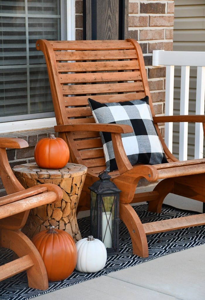 Wooden chairs, black and white pillows, white and orange pumpkins and a black and white rug on front porch.