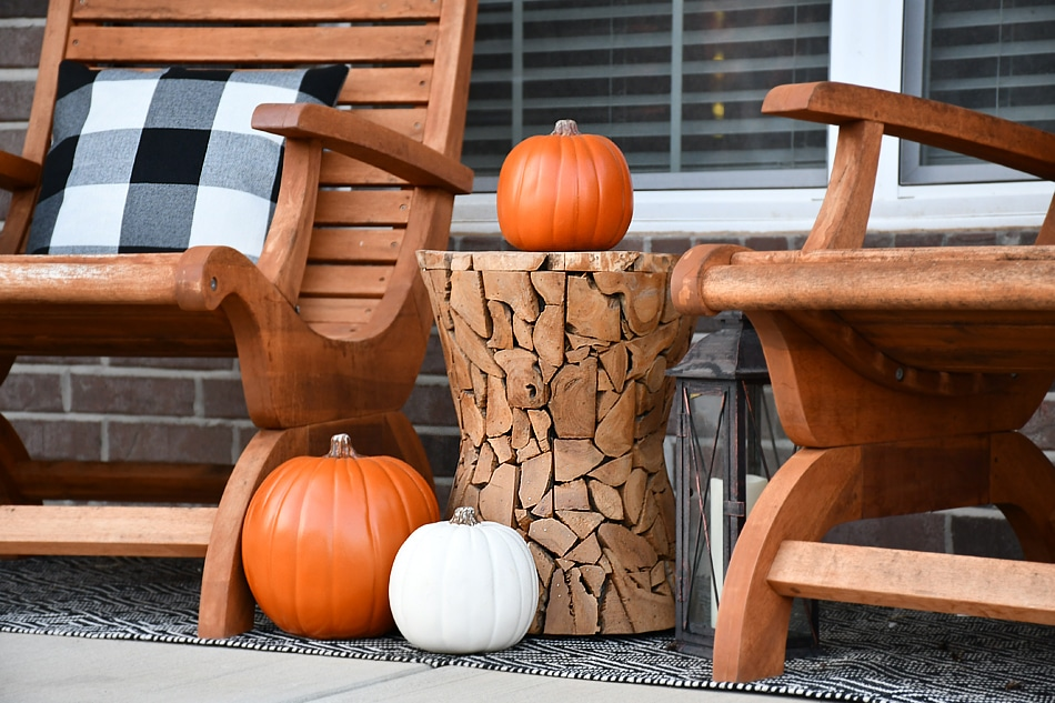 Wooden side table with a pumpkin on it on the front porch.