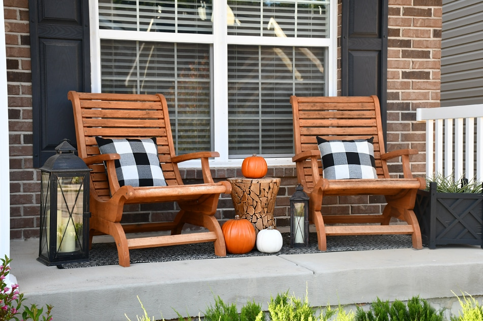 Two wooden chairs on the fall front porch with black and white checkered pillows on them.