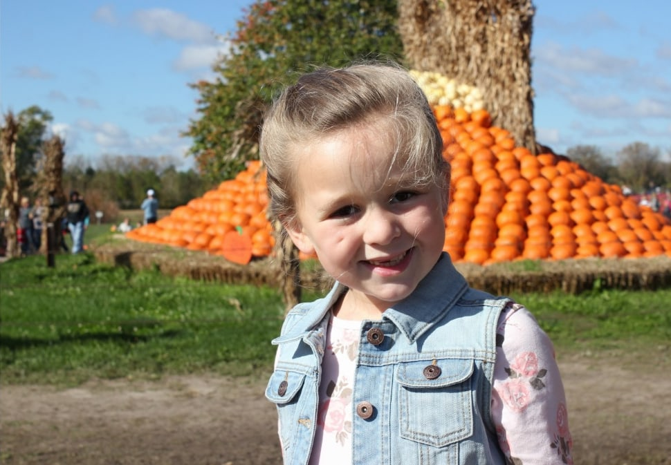 Girl smiling at the pumpkin patch.