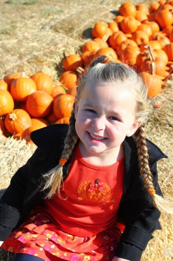 Girl with braids sitting by a row of pumpkins.