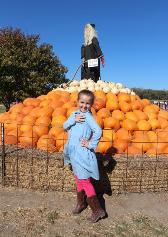 Girl in jean dress in front of pumpkin display.