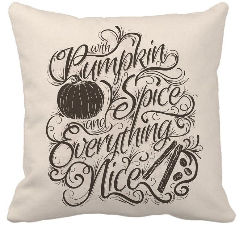 Beige and black pillow with pumpkin spice written on it.
