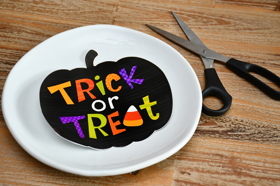 Cutting out the black trick or treat sticker.