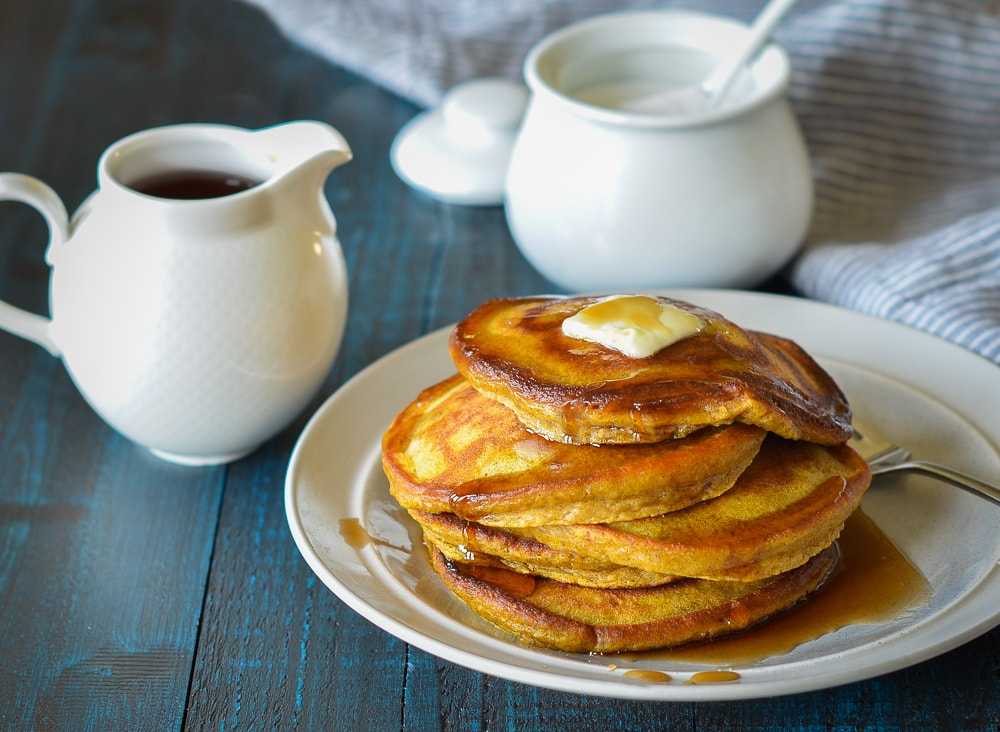 Pumpkin pancakes on a white plate with syrup on top on a blue table.