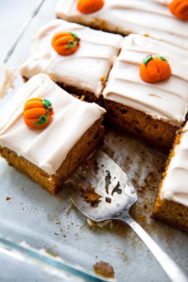 Pumpkin cake with cream cheese icing and mini pumpkins on top.