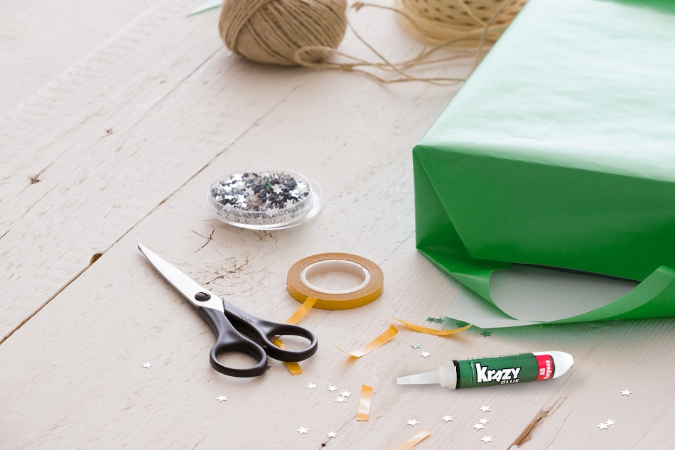 Scissors, twine, a half wrapped present, tape and Krazy Glue beside them.