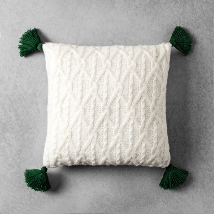 A white knit pillow with green tassels.