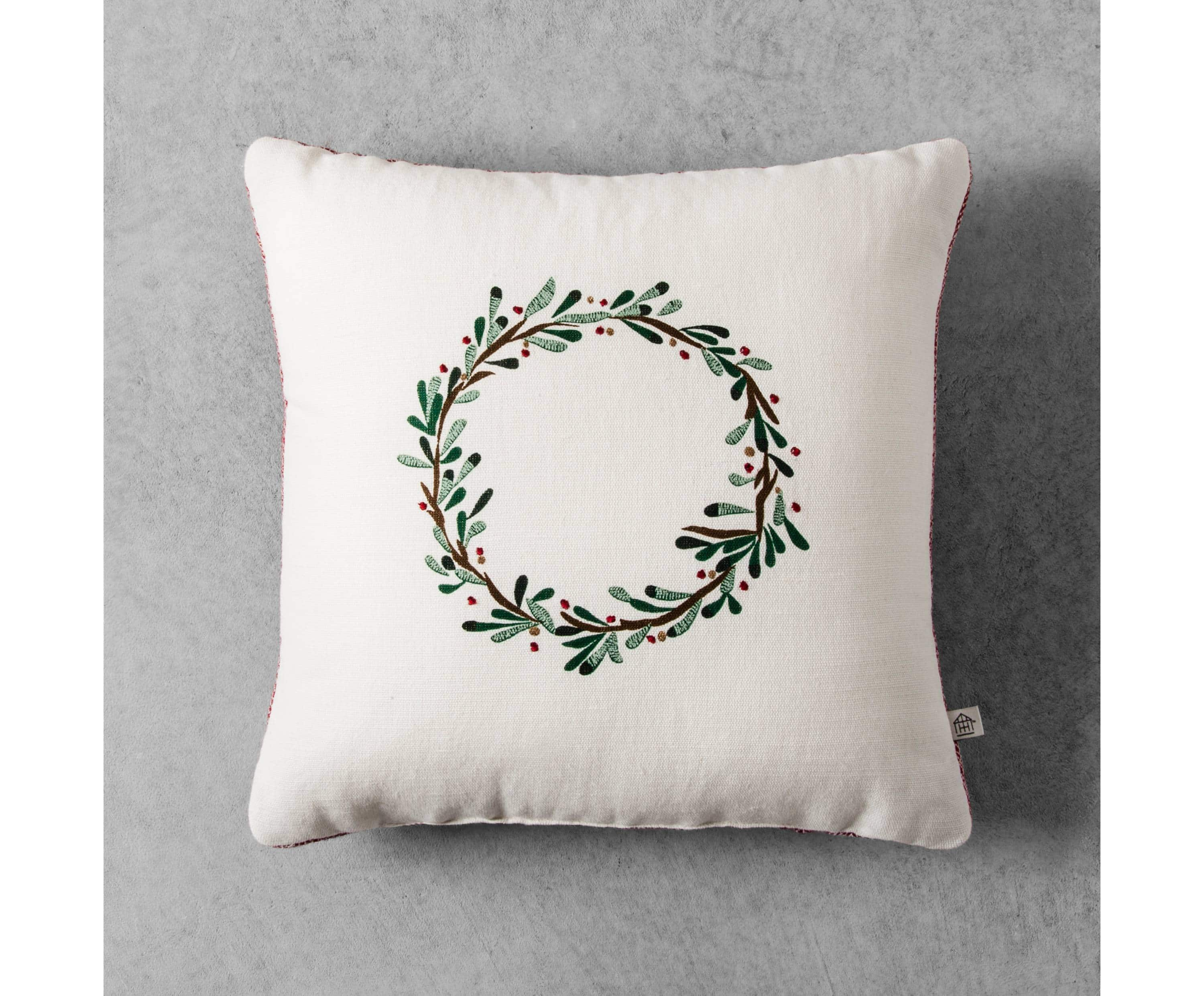 A white pillow with a green wreath motif on it.