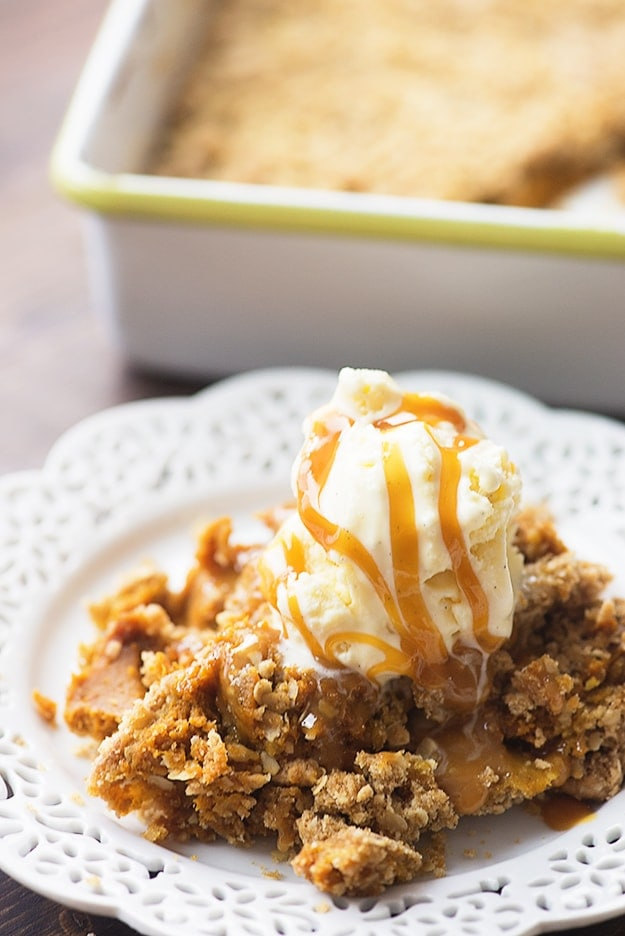 Pumpkin cobbler on a plate with ice cream on top of it, and caramel syrup drizzled.