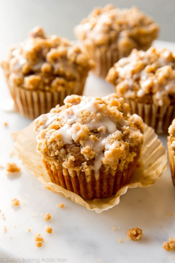Pumpkin muffins on the counter with some icing on top.