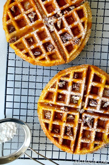 Pumpkin waffles a cooling rack with icing sugar on top.