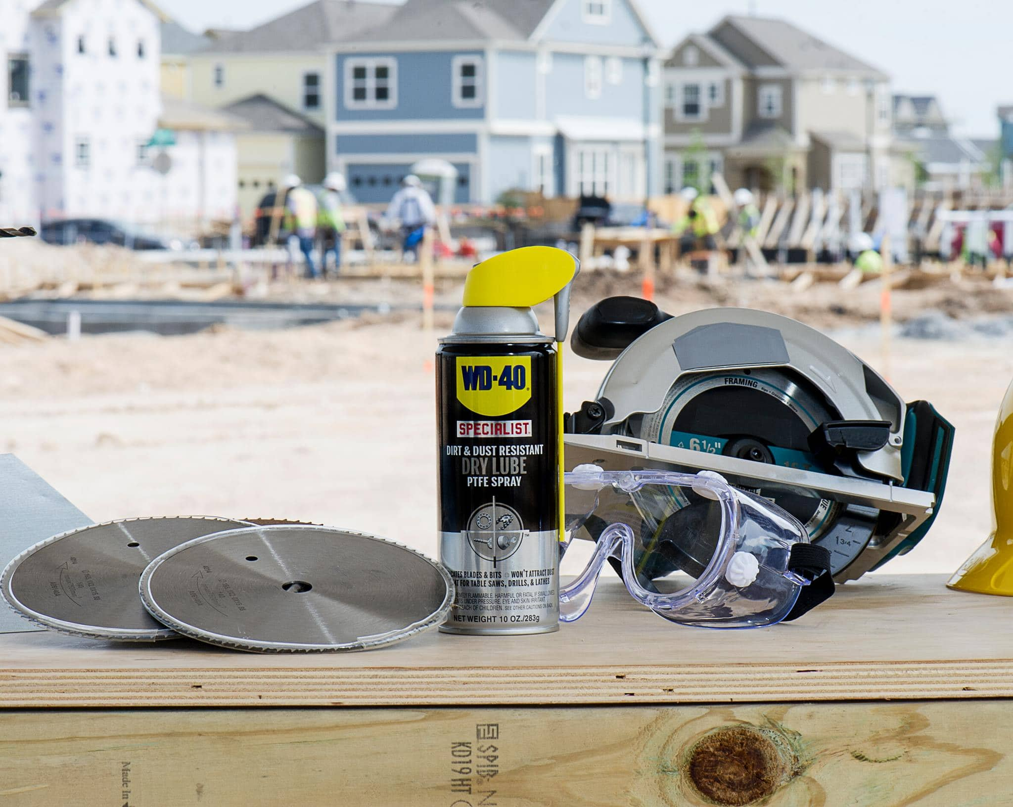 The WD-40 on a workbench outside with a saw beside it.