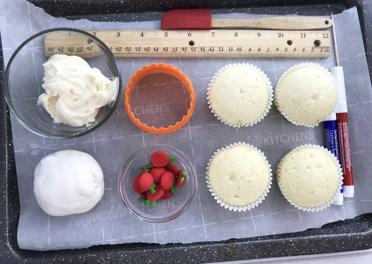 Cupcake batter, baked cupcakes and rulers on a pan.
