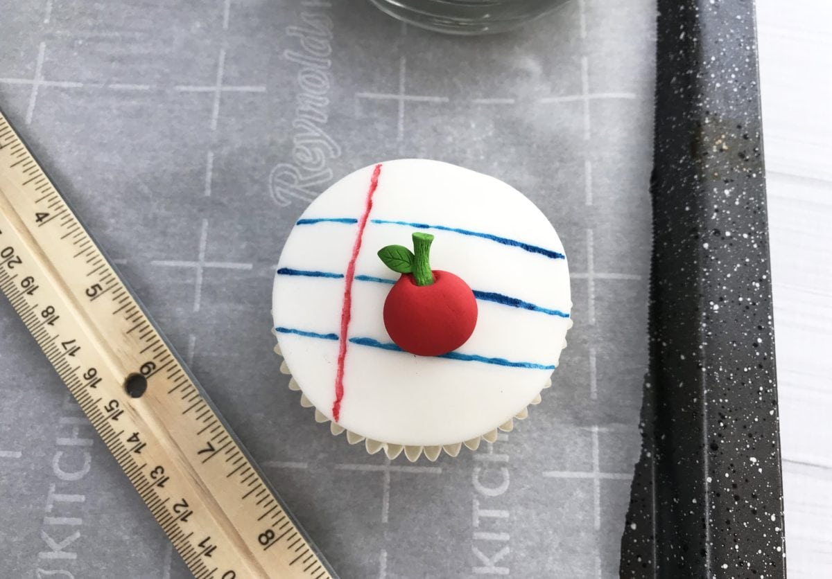 The decorated fondant on top of the cupcake with a ruler beside it.