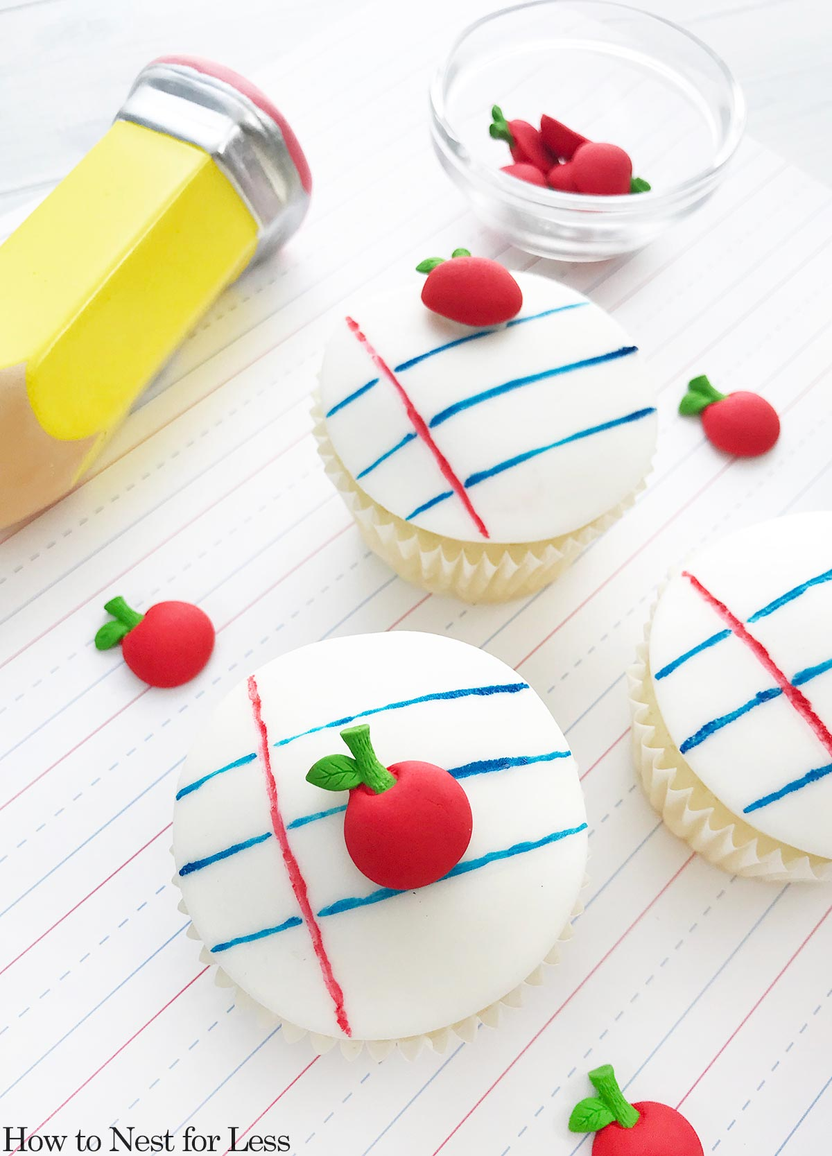 White, blue, and red stripes on cupcake with an iced red apple on top.