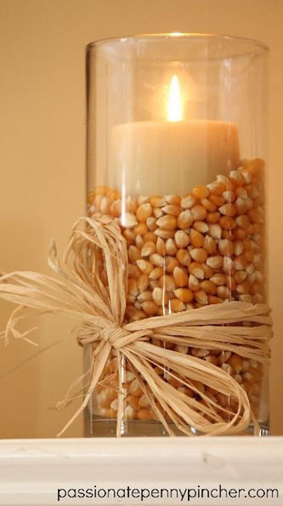 Popcorn kernels in a glass vase with a candle on top and sisal rope tied around the base in a bow.