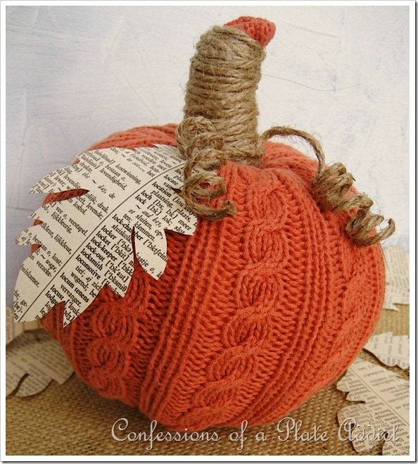 A pumpkin wrapped in an old orange sweater with a cut out leaf at stem.