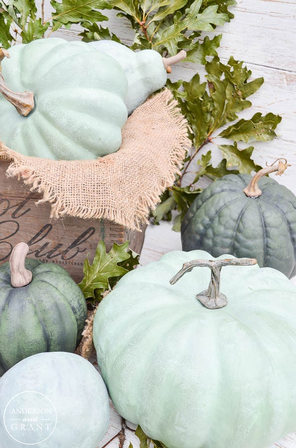 Painted pumpkins in light blues and greys sitting on the porch.