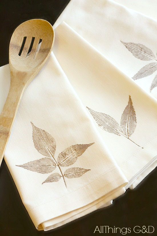 Leaves stamped on a white napkin with a wooden ladle laying on top.