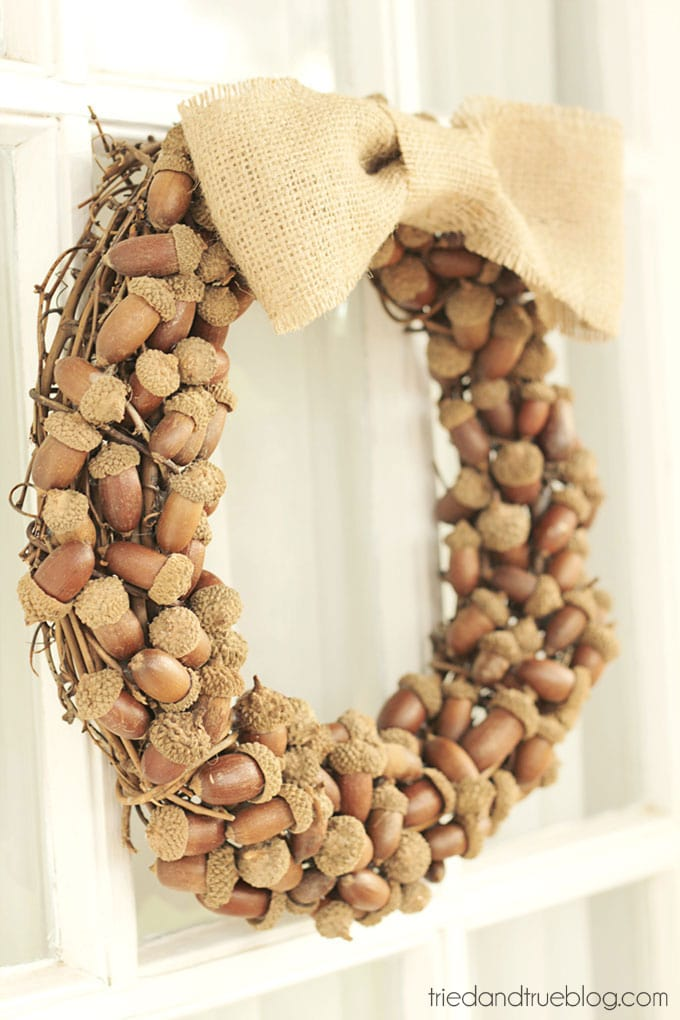 A wreath made f acorns hanging on the front door.