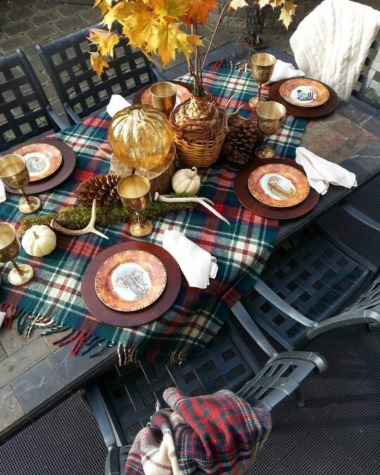 A fall table setting with a plaid runner and centrepiece with maple leaves.