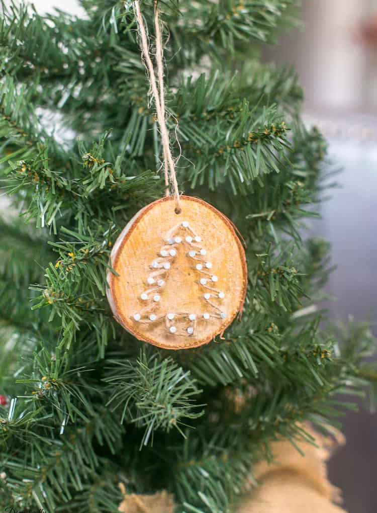 A wooden ornament with a simple Christmas tree on it.