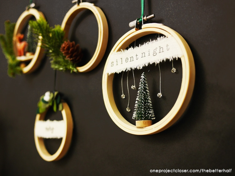 Embroidery hoops with mini trees and pine cones decorated for the holidays.