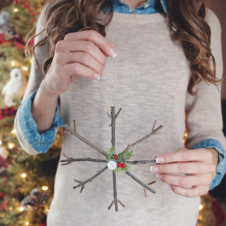 Twigs strung together to look like a star being held by a girl.