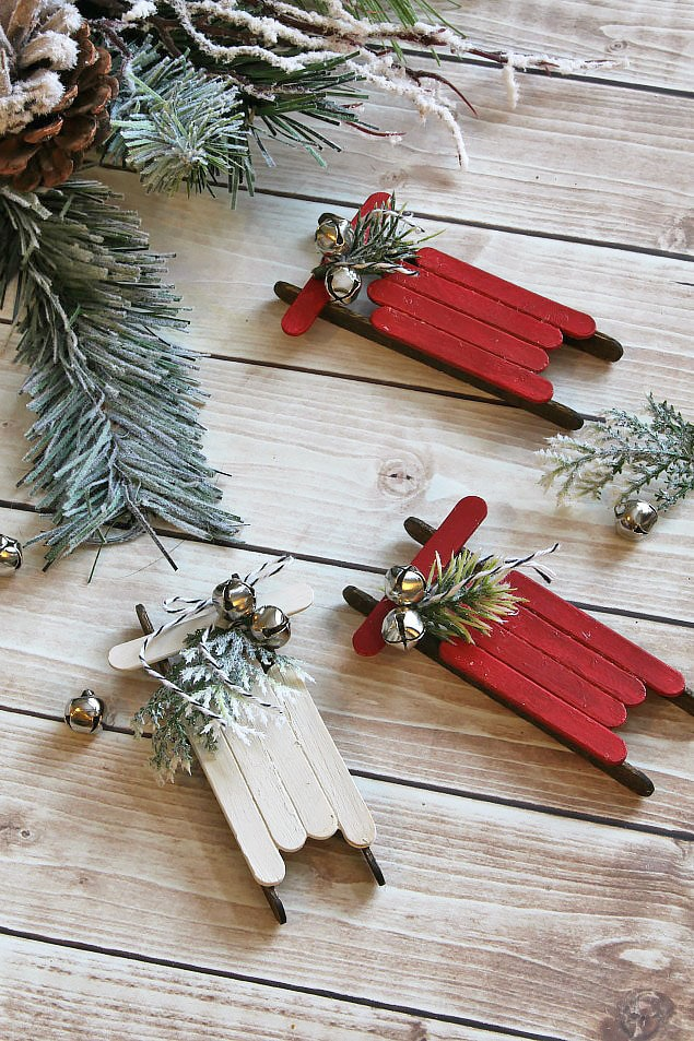 Popsicle stick sleighs in red and white with bells lying on the ground under the tree.