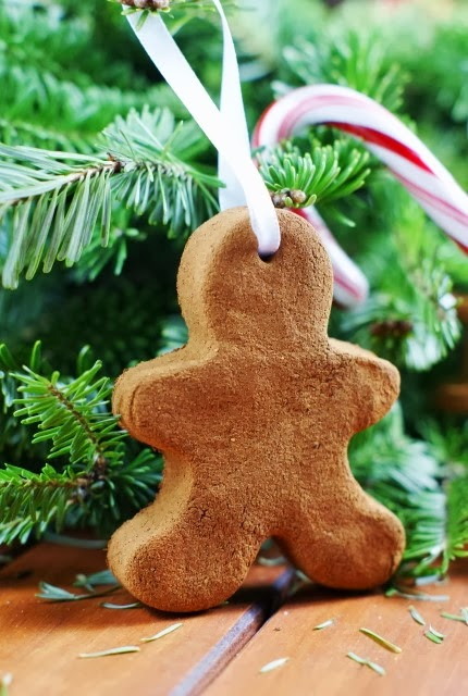 A DIY gingerbread man with a hole in the top and ribbon in the hole to be tied as an ornament.