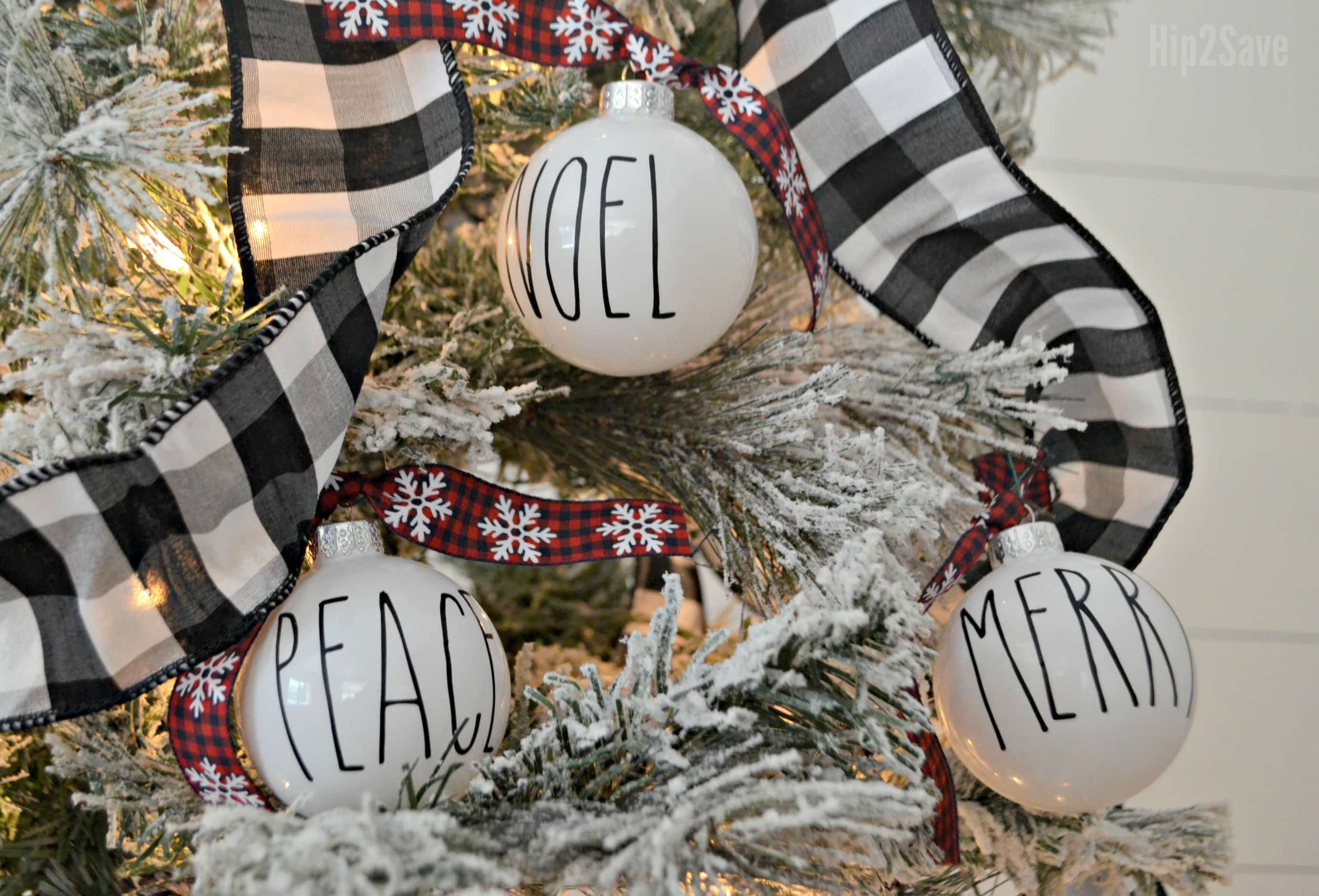 White ornaments with Noel, Peace, and Merry written on them in black sharpie.
