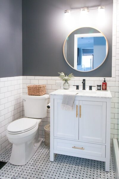 White subway tile and white vanity in bathroom with dark gray walls
